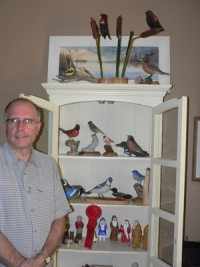 James Hooey beside cabinet of Bird Carvings
