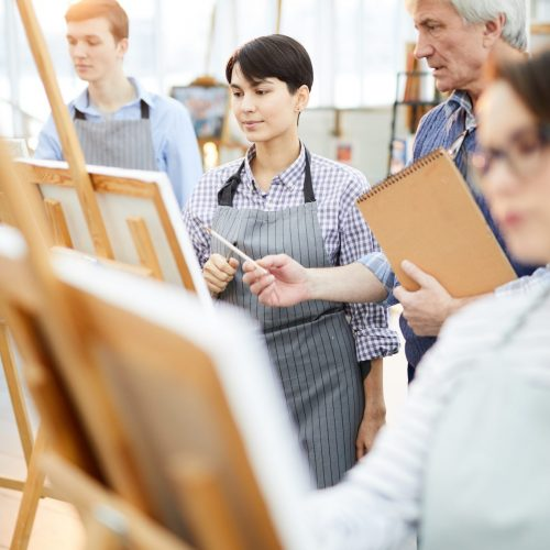Portrait of art students painting at easels in art class with mature teacher helping them, copy space